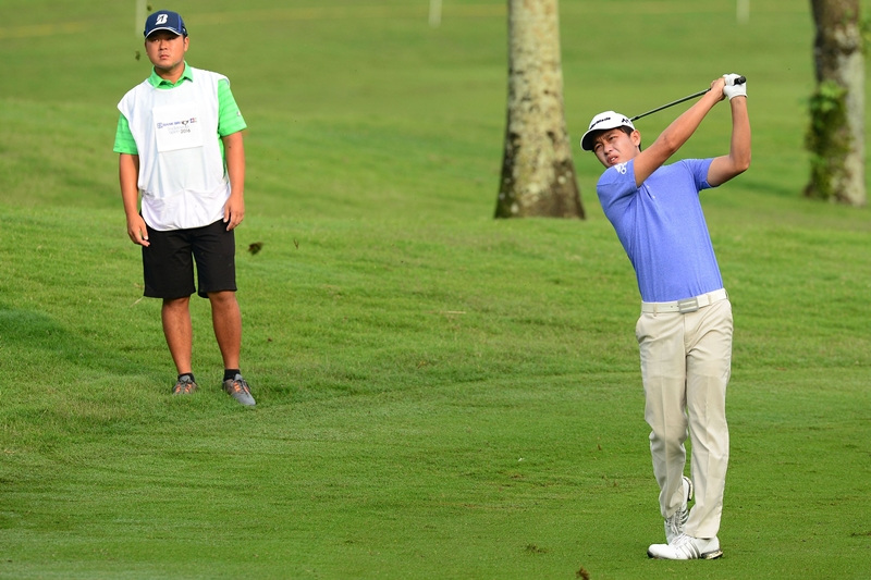 Ben Leong plays a shot as his caddie Lam Yu Shuen watches on ©Arep Kulal| Asian Tour